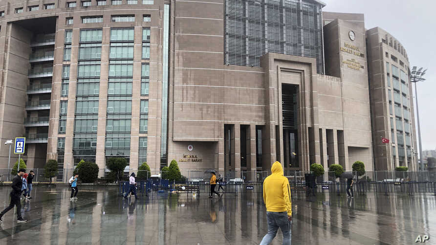 People walk outside the Justice Palace, in Istanbul, Sept. 20, 2019. Two reporters appeared in court accused of trying to undermine Turkey's economic stability.