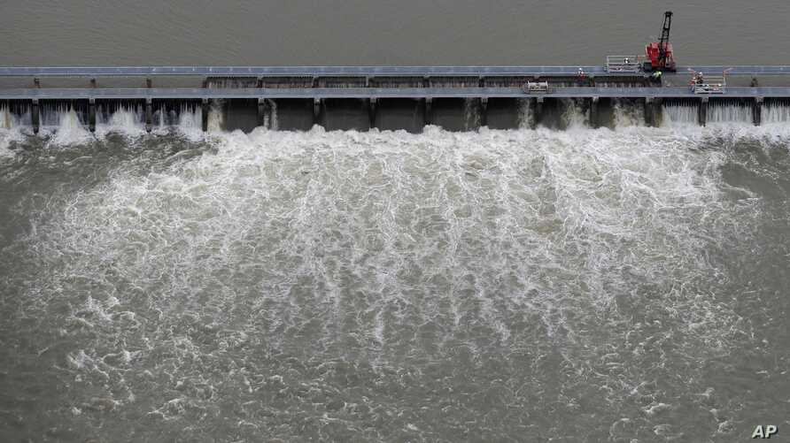 FILE- Workers open bays of the Bonnet Carre Spillway to divert rising water from the Mississippi River to Lake Pontchartrain, up