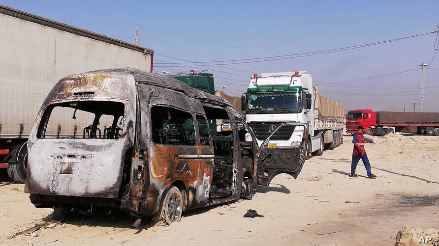 A destroyed minibus sits near an Iraqi army checkpoint about 10 km (6 miles) south of Karbala, Iraq, Sept. 21, 2019. A bomb exploded on a minibus outside the Shiite holy city of Karbala Friday night, killing and wounding civilians, Iraqi officials said.