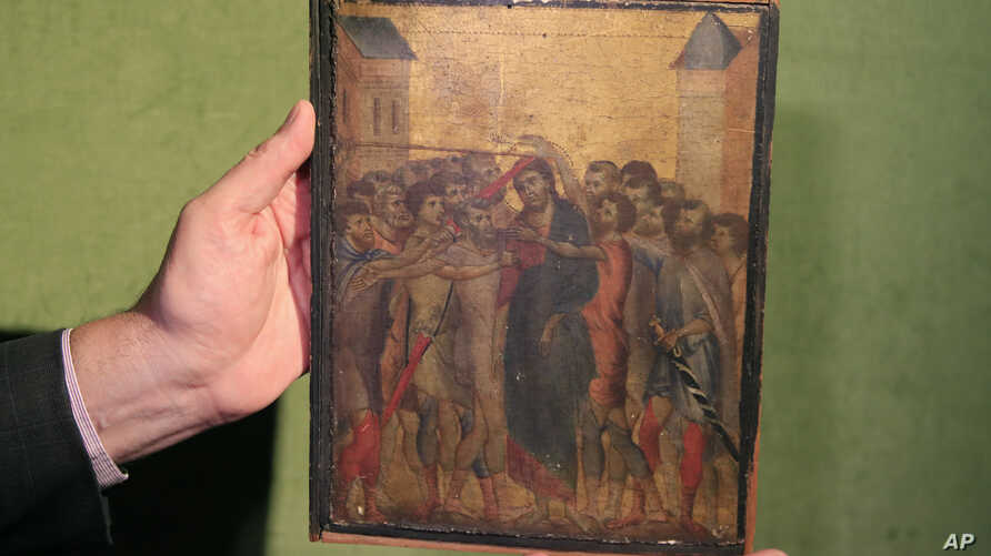 Art expert Stephane Pinta points to a 13th century painting by Italian master Cimabue in Paris, Sept. 24, 2019.