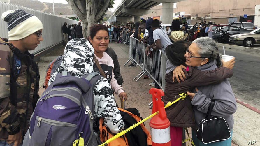 Luz Bertila Zazueta, 75, of Tijuana, right, hugs farewell to a Peruvian woman and her children whose numbers were called Sept. 26, 2019 to claim asylum in San Diego. Zazueta persuaded a neighbor to let the family live in his empty house for free during their six-month wait.