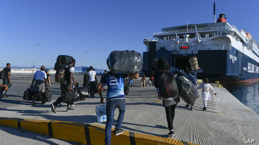 Refugees and Migrants disembark on a ferry with destination the port of Piraeus, on the northeastern Aegean island of Lesbos, Greece, Sept. 30, 2019.