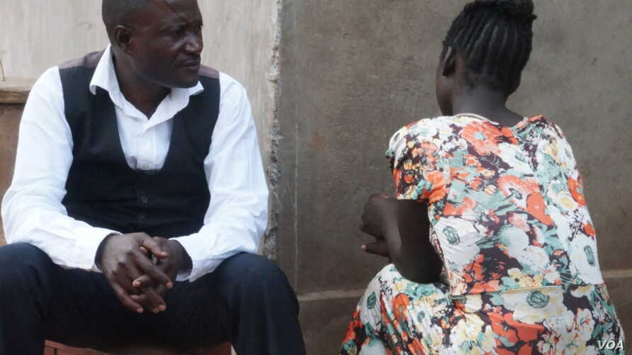 """Caleb Ng'ombo , Director of People Serving Girls At Risk, talks to """"Maggie"""" a victim of child trafficking, in Neno district in southern Malawi."""