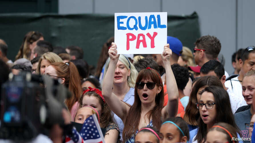 FILE - Females chant for equal pay for women as they wait for the United States women's national soccer team in New York City, July 10, 2019.