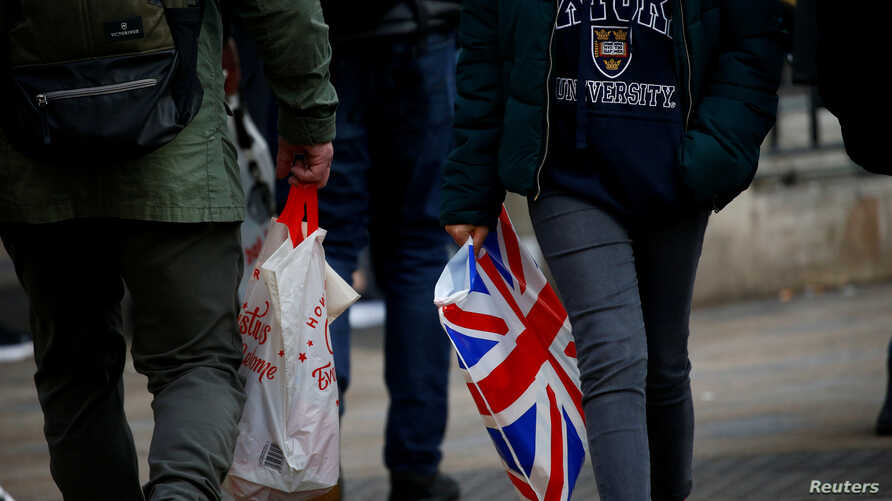 FILE - Shoppers carry shopping in plastic bags in the West End, in London, Britain, Dec. 27, 2018.