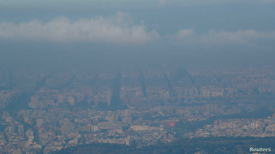FILE - Pollution and clouds are seen over the sky of Barcelona, Spain, July 25, 2019.
