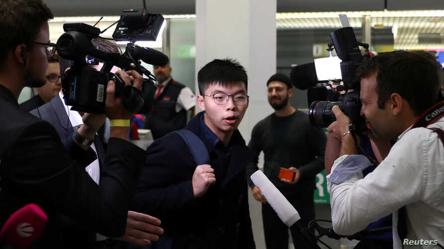 Hong Kong's pro-democracy activist Joshua Wong is surrounded by journalists after arriving at Tegel Airport in Berlin, Germany, Sept. 9, 2019.