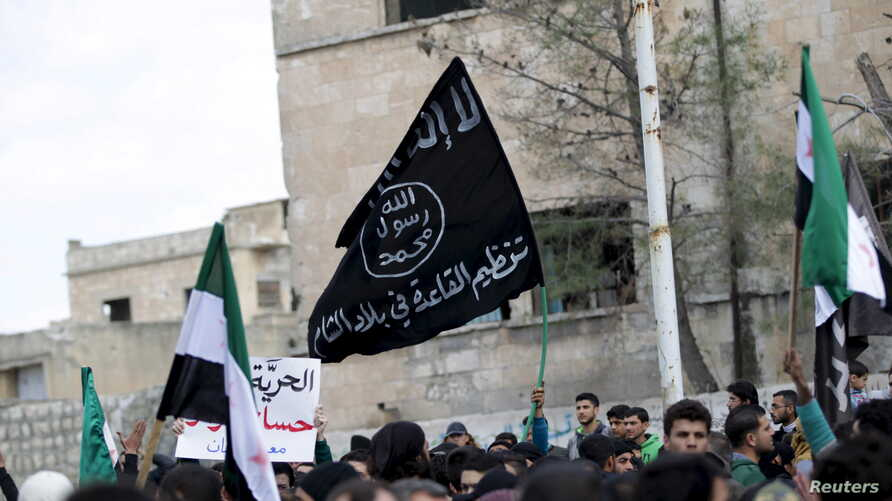 Protesters carry Al-Qaida flags during an anti-government protest after Friday prayers in the town of Marat Numan in Idlib province, Syria, March 11, 2016.