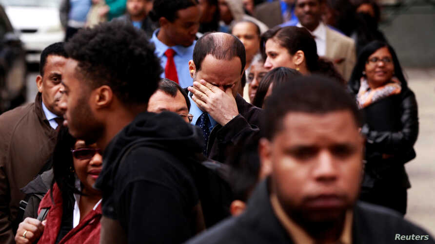 A man rubs his eyes as he waits in a line of jobseekers, to attend the Dr. Martin Luther King Jr. career fair held by the New York State department of Labor in New York, April 12, 2012.