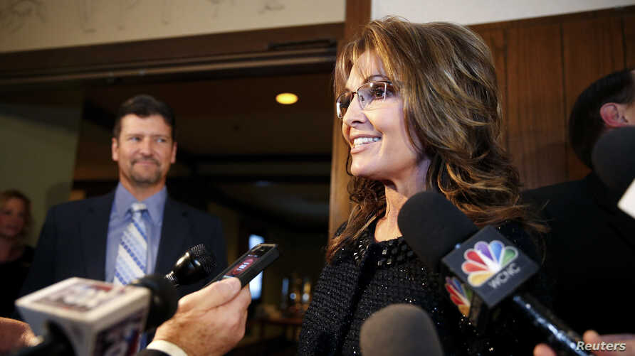 FILE - Former Republican governor of Alaska Sarah Palin speaks to members of the media as her husband Todd looks on before an event in Asheville, North Carolina, Nov. 7, 2013.