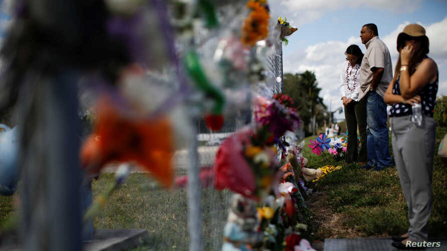 FILE - People mourn in front of flowers placed in the fence of the Marjory Stoneman Douglas High School following a mass shooting in Parkland, Florida, Feb. 18, 2018.