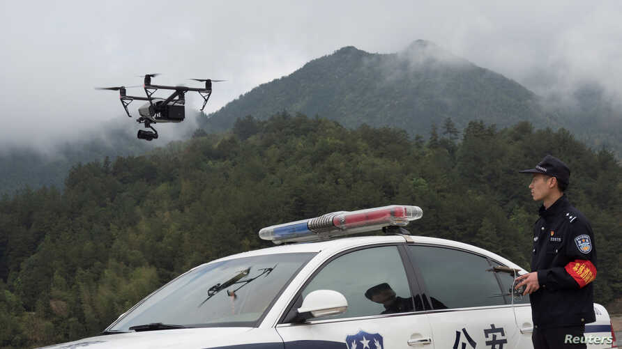 FILE - A police officer of the Forest Public Security Bureau operates a drone in Lishui, Zhejiang province, China, April 4, 2018. Police in China used drones to track down a fugitive who had escaped from a prison camp 17 years ago.