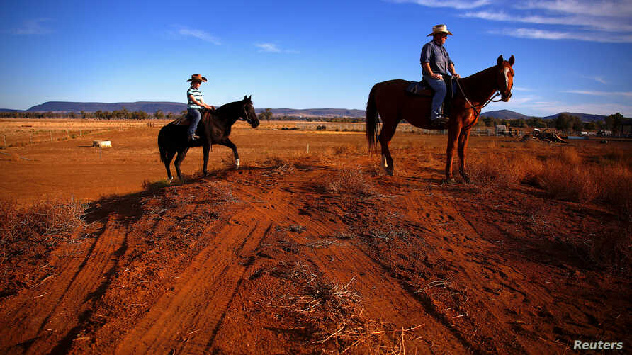 Farmer Scott Cooper and his daughter Charlie ride their horses along a fence in a drought-affected paddock on their property nam