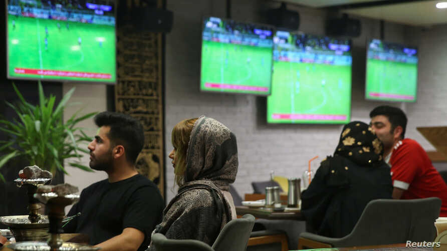 FILE - Iranian women watch a football match at a cafe in Tehran, Iran, Sept. 15, 2019.