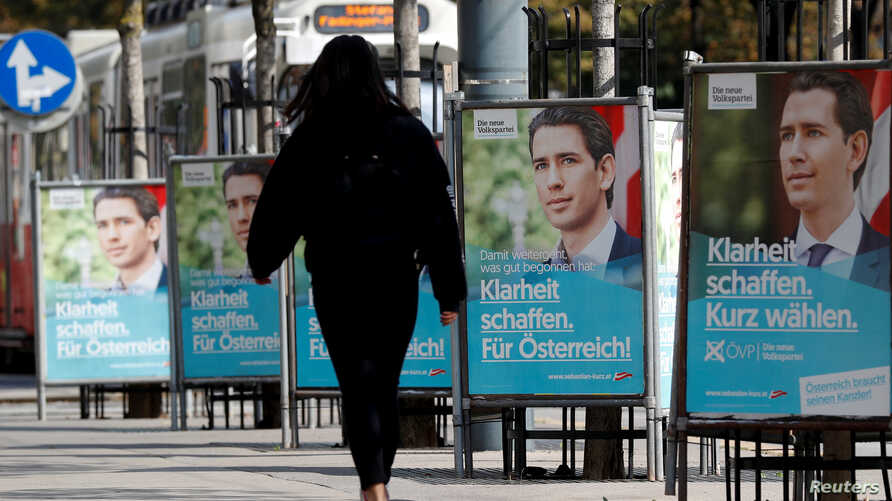 A person passes election campaign posters of the head of Austria's Peoples Party (OeVP) and former Chancellor Sebastian Kurz in Vienna, Austria, Sept. 23, 2019.