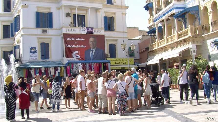 Tourists at the medina in Tunis are flanked by campaign posters, Sept. 13, 2019. (L. Bryant/VOA)
