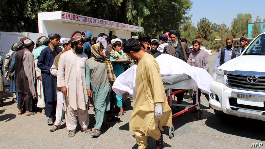 Afghan villagers carry a dead body on a stretcher outside a hospital following an airstrike in Lashkar Gah, the capital of Helmand province on Sept. 23, 2019.
