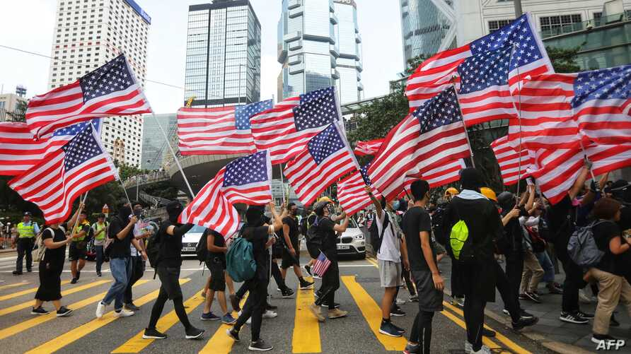 Protesters wave American flags as they march from Chater Garden to the U.S. consulate in Hong Kong, Sept. 8, 2019, to call on the U.S. to pressure Beijing to meet their demands.