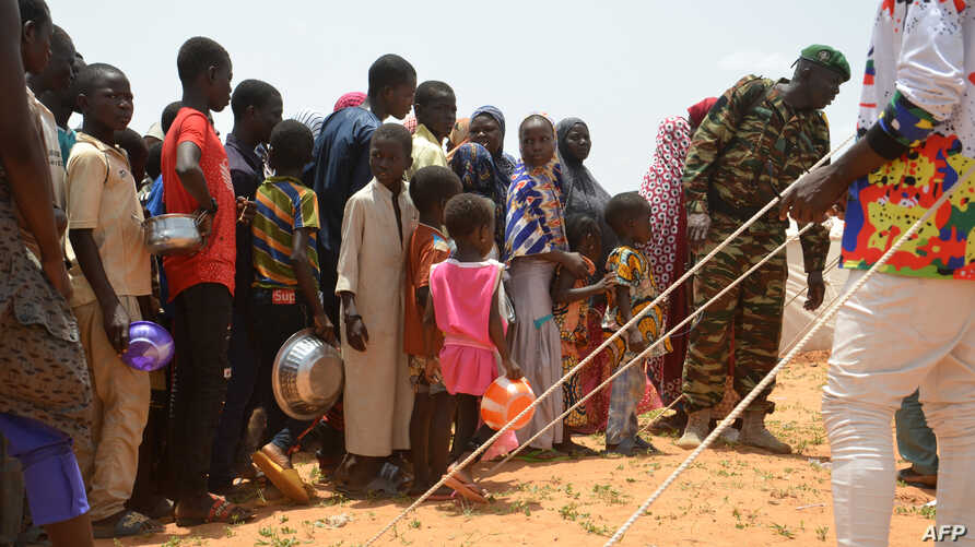 Children queue for food distributed by an NGO in the makeshift camp of Saguia near the capital Niamey, on Sept. 11, 2019, after the Niger river floods forced residents from the area.