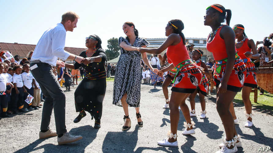 """Prince Harry, Duke of Sussex and Meghan, Duchess of Sussex, dance during a visit to the """"Justice desk"""", an NGO in the township of Nyanga in Cape Town, as they begin their tour of the region."""