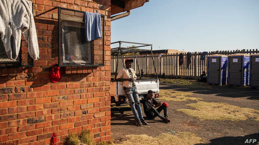 Two men rest outside the Tsolo Community Hall in Johannesburg's Katlehong township, Sept. 9, 2019, where around 250 people, are hosted after being displaced by anti-foreigner violence that hit South Africa's financial capital.