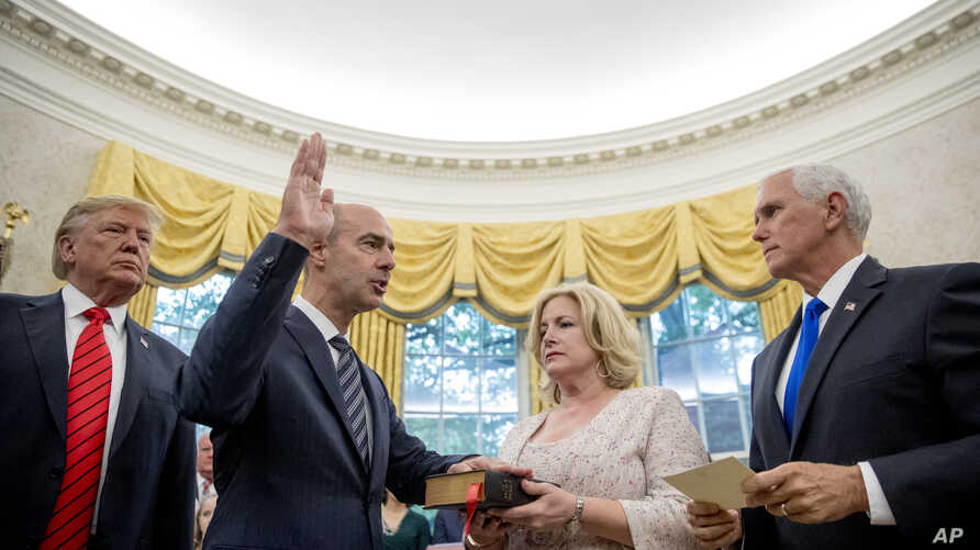 President Donald Trump watches as Vice President Mike Pence, right, administers the oath of office for Eugene Scalia, second from left, to be the next Labor Secretary during a ceremonial swearing-in ceremony at the White House, Sept. 30, 2019.