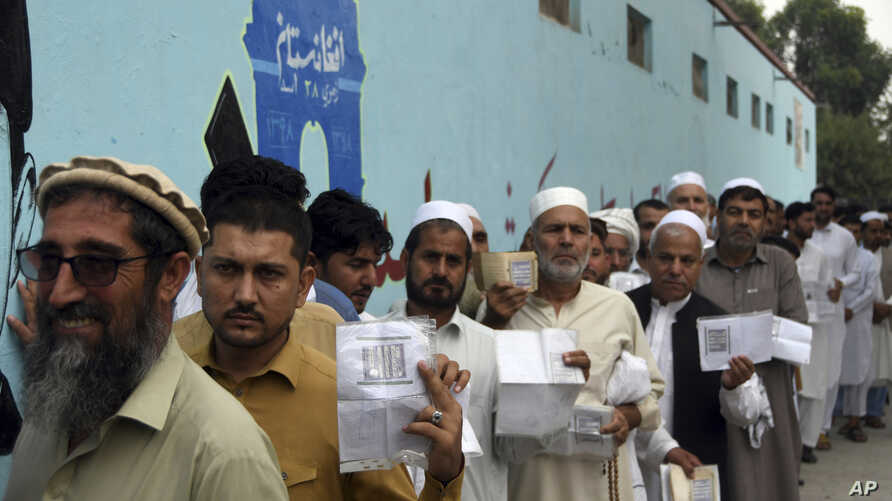 Men line up to cast their votes outside a polling station in Jalalabad east of Kabul, Afghanistan, Sept. 28, 2019.