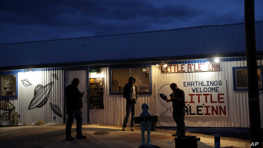 "People stand around the Little A'Le'Inn during an event inspired by the ""Storm Area 51"" internet hoax, Sept. 19, 2019, in Rachel, Nevada. Hundreds have arrived in the desert after a Facebook post invited people to ""see them aliens."""