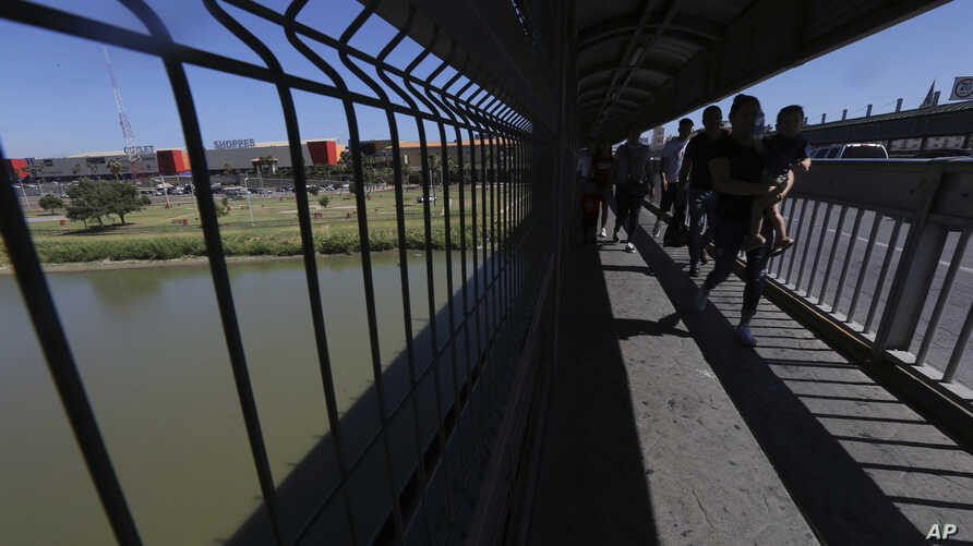 FILE - People walk back to Mexico on International Bridge 1 Las Americas, a legal port of entry which connects Laredo, Texas, in the U.S. with Nuevo Laredo, Mexico, July 18, 2019.