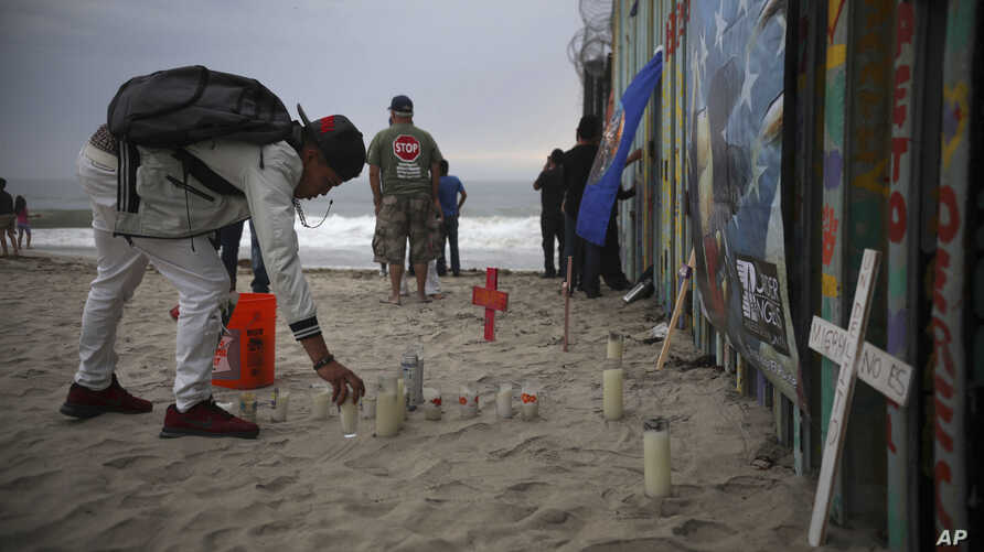 Candles are placed next to the border fence that separates Mexico from the U.S., in memory of migrants who have died during their journey toward the U.S., in Tijuana, Mexico, June 29, 2019.