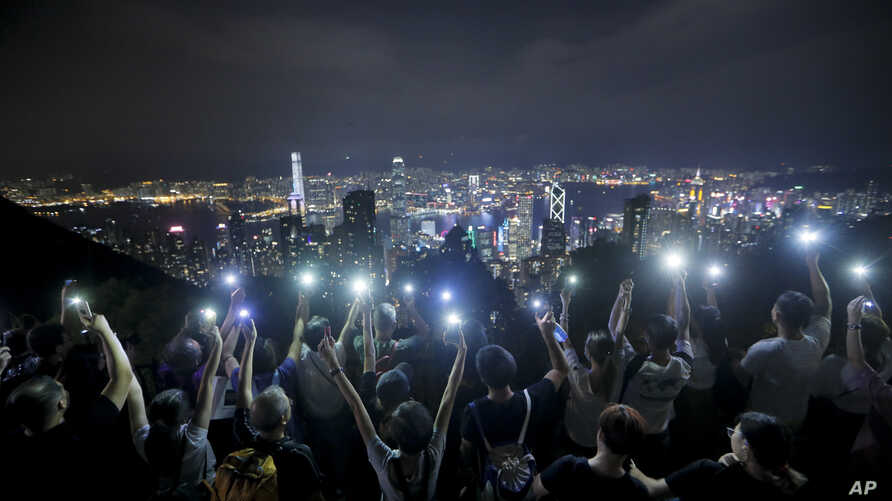 Demonstrators hold up their mobile phones as they form a human chain at the Peak, a tourist spot in Hong Kong, Sept. 13, 2019.