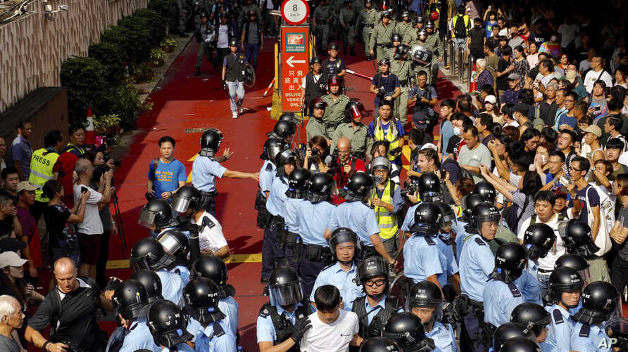 Riot police move in after fights broke out between China supporters and anti-government protesters at Amoy Plaza in the Kowloon Bay district in Hong Kong, Sept. 14, 2019.