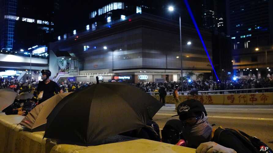 Protesters take cover as they face policemen in Hong Kong, Sept. 28, 2019.