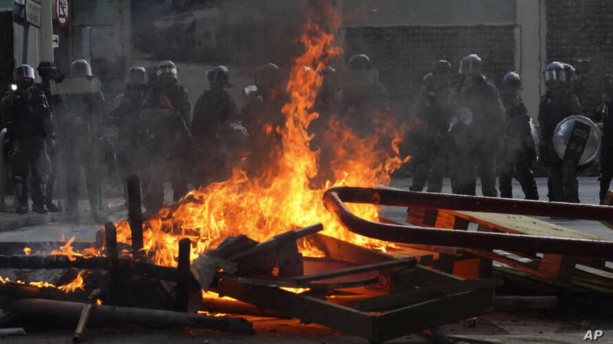 Police face a burning barricade during protests, Sept. 21, 2019, in Hong Kong.