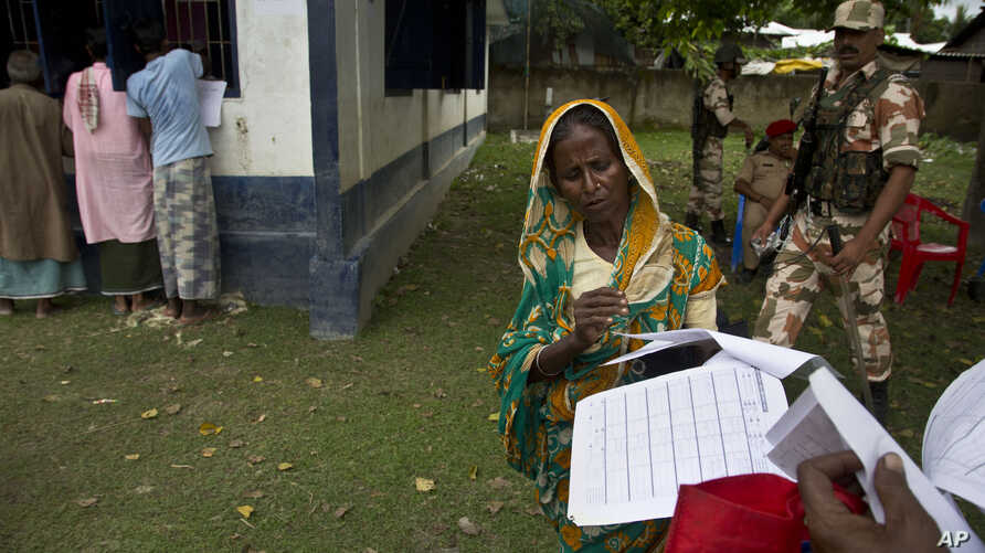 a woman checks her papers as villagers check their names in the final list of National Register of Citizens in Morigaon district, Assam, India, Aug. 31, 2019.