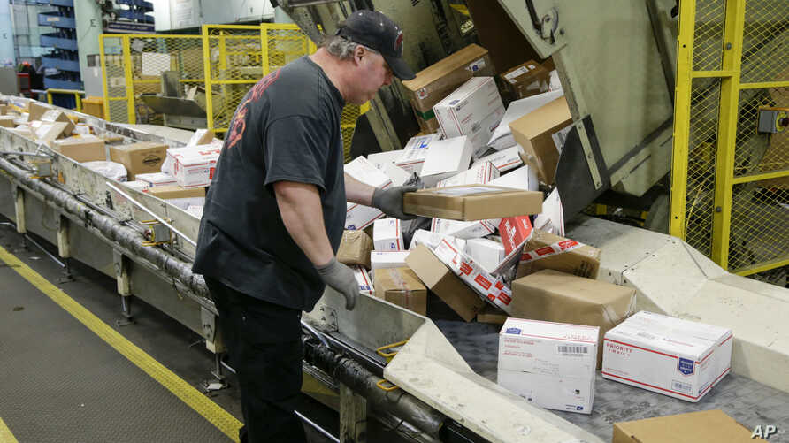 FILE -  Steve Robino arranges packages on a conveyor belt at the main post office in Omaha, Neb., Dec. 14, 2017.