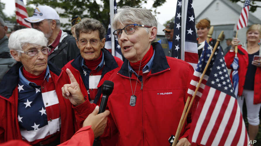 Elaine Greene, right, accompanied by JoAnn Miller, and Carmen Footer, speaks to a reporter on Main Street, Sept. 11, 2019, in Freeport, Maine.