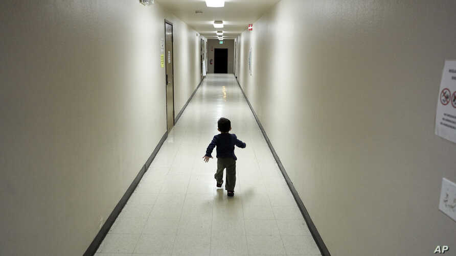FILE - A boy who was detained with migrants at the U.S.-Mexico border runs down a hallway after arriving from an immigration detention center at a shelter in San Diego, California, Dec. 11, 2018.