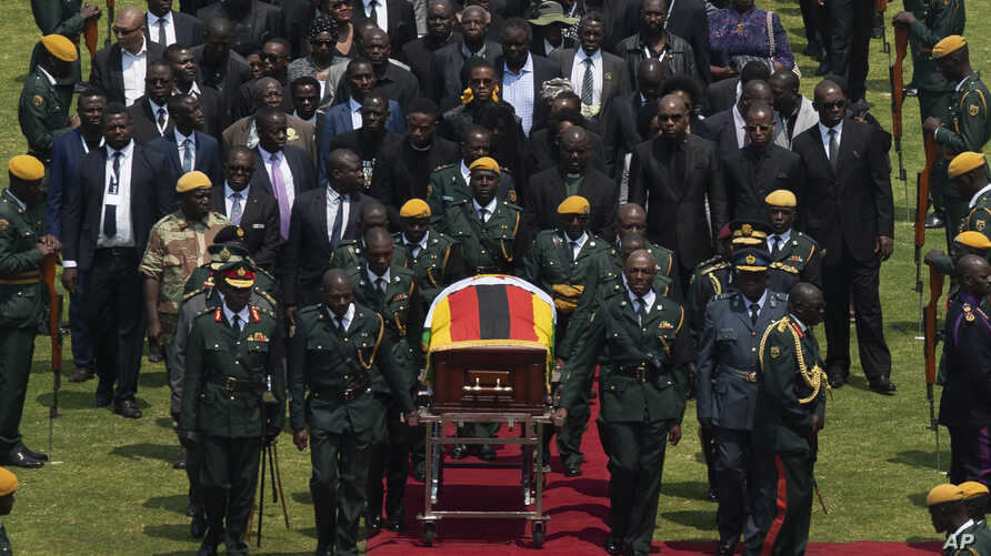 The casket of former Zimbabwean president Robert Mugabe, covered by the national flag and followed by family and dignitaries, arrives for a state funeral at the National Sports Stadium, in the capital Harare, Zimbabwe, Sept. 14, 2019.