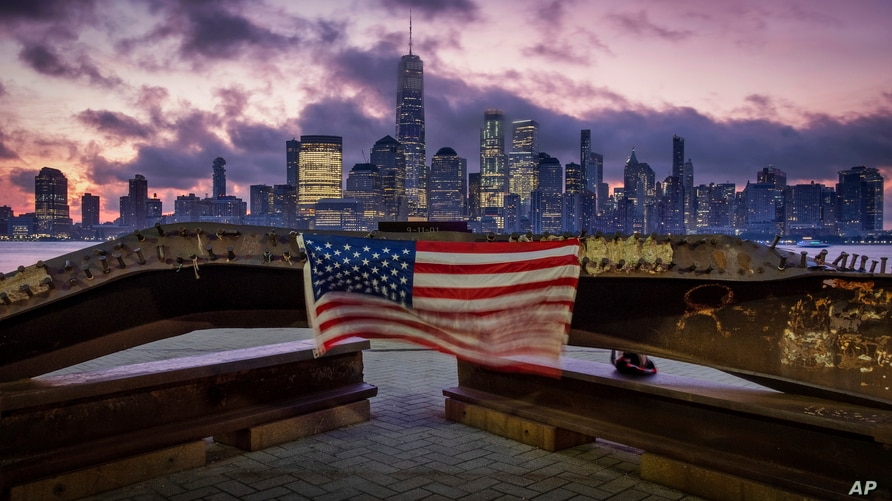 A U.S. flag hanging from a steel girder, damaged in the Sept. 11, 2001 attacks on the World Trade Center, blows in the breeze at a memorial in Jersey City, New Jersey, Sept. 11, 2019