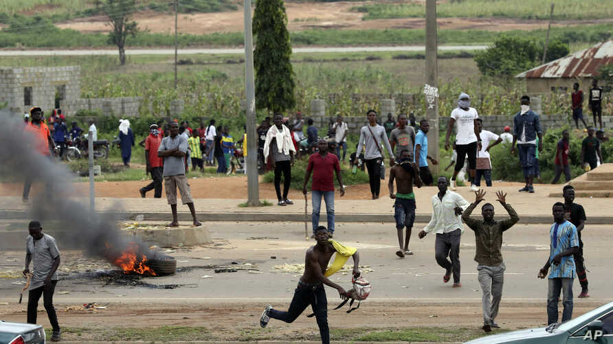 Protesters throw rocks at policemen during an attack on South African business, in Abuja, Nigeria, Sept. 4, 2019.