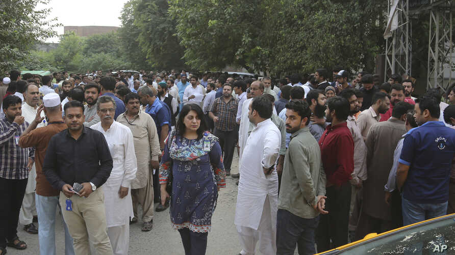 People stand outside after an earthquake is felt in Lahore, Pakistan, Sept. 24, 2019.