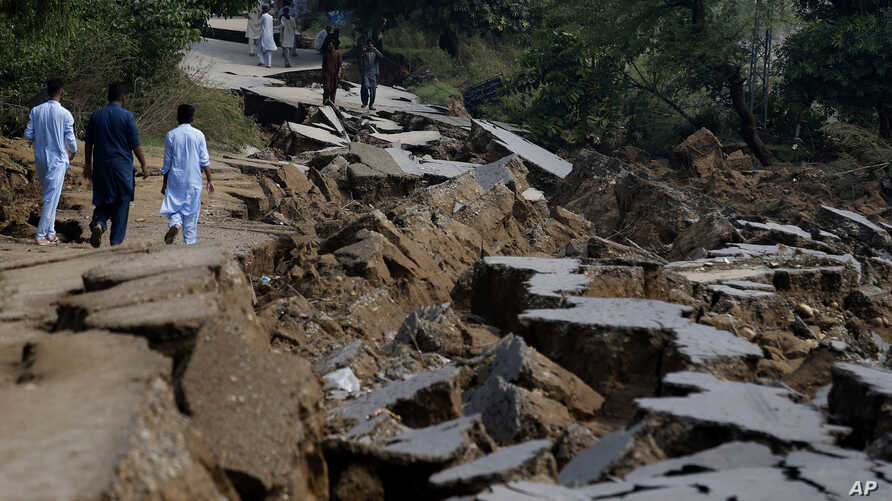 Residents walk alongside a damaged portion of a road caused by a powerful earthquake in Jatlan near Mirpur, in northeast Pakistan.