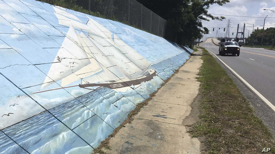 FILE - Traffic passes a mural of the slave ship Clotilda along Africatown Blvd. in Mobile, Alabama, May 30, 2019.