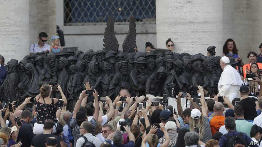 Pope Francis unveils a sculpture on the occasion of the World Day for Migrant and Refugee, in St. Peter's Square, at the Vatican, Sept. 29, 2019.