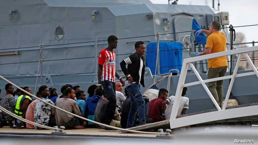 FILE - A police officer speaks to rescued migrants after they arrived on an Armed Forces of Malta patrol boat in Valletta's Marsamxett Harbour, Malta, Sept. 21, 2019.