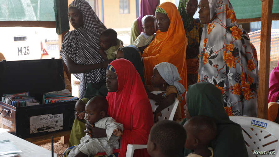 FILE - Women with their children wait to see doctors at a clinic operated by Doctors without Borders in Bagega village in northeastern state of Zamfara, Aug. 14, 2013.