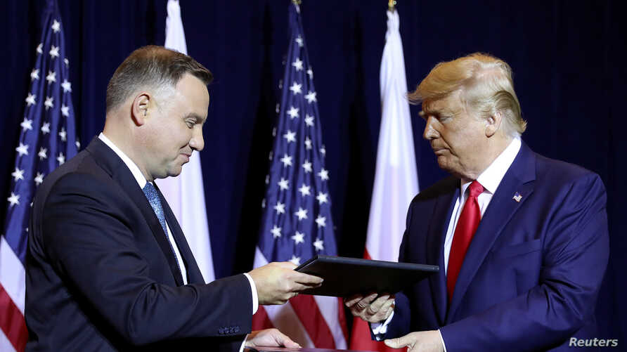 """U.S. President Donald Trump and Poland's President Andrzej Duda exchange documents after signing a """"joint declaration enhancing defense cooperation"""" prior to their bilateral meeting on the sidelines of the annual U.N. General Assembly in New York, Sept. 23, 2019."""