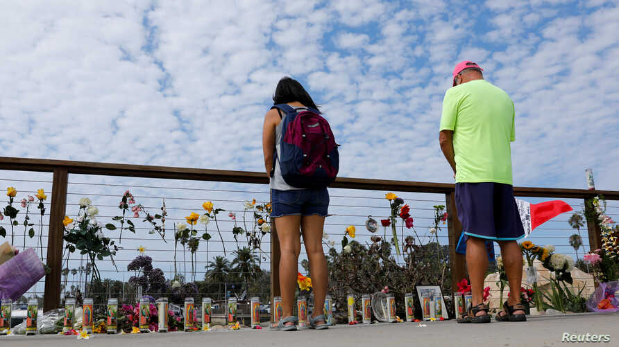 People stop to pause over a makeshift memorial near Truth Aquatics as the search continues for those missing in a pre-dawn fire that sank a commercial diving boat off a Southern California island near Santa Barbara, California, Sept. 3, 2019.