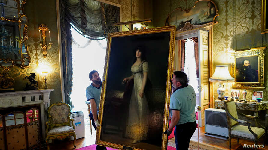 "Workers carry ""The Marquise of Lazan"" painting by the Spanish painter Francisco Goya at Liria Palace in Madrid, Spain, Sept. 9, 2019."